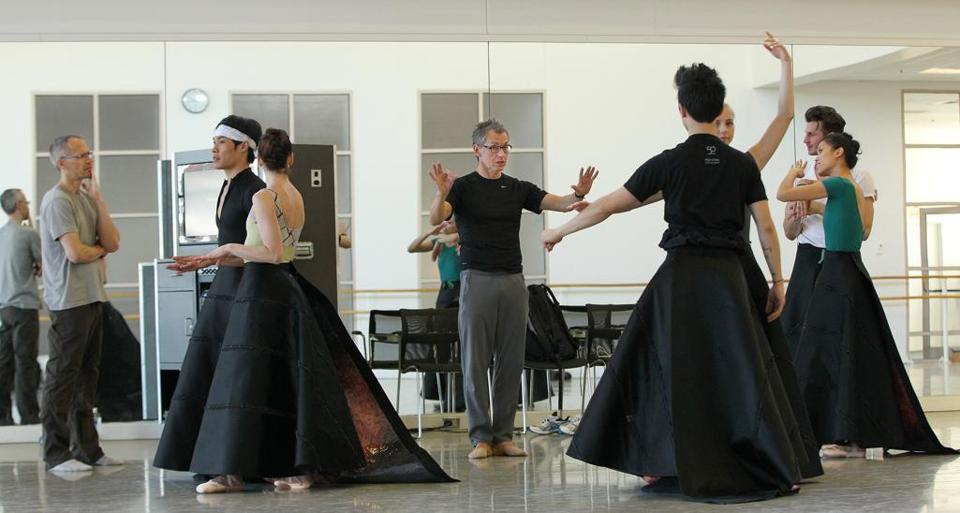 "Choreographer Jorma Elo works with Boston Ballet dancers in rehearsal for ""C. to C. (Close to Chuck),"" his dance set to music by Philip Glass and an homage to artist Chuck Close. The dancers' skirts were designer Ralph Rucci's idea of connecting the costumes to the backdrop, self-portraits by Close."